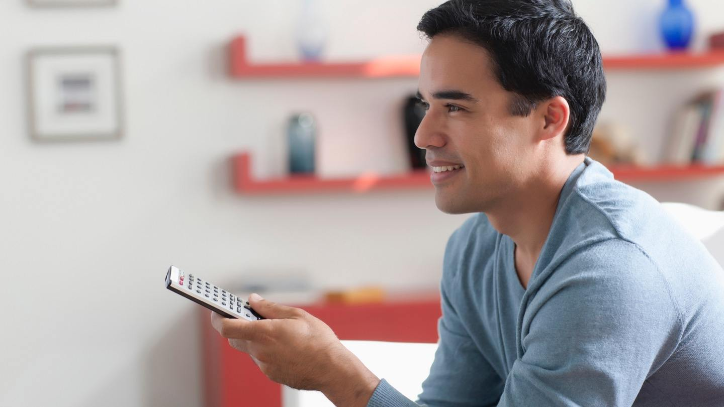 man watching DIRECTV learning how to reset DIRECTV remote