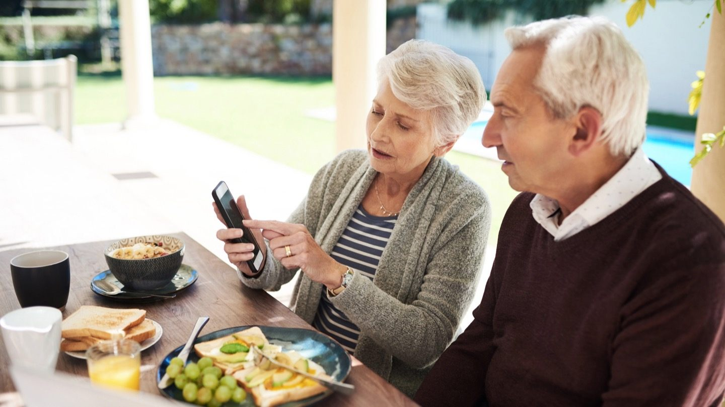 elderly couple looking on phone to pause wifi service for seasonal hold