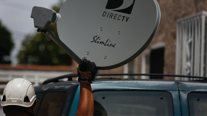 Technician holding a DIRECTV satellite dish