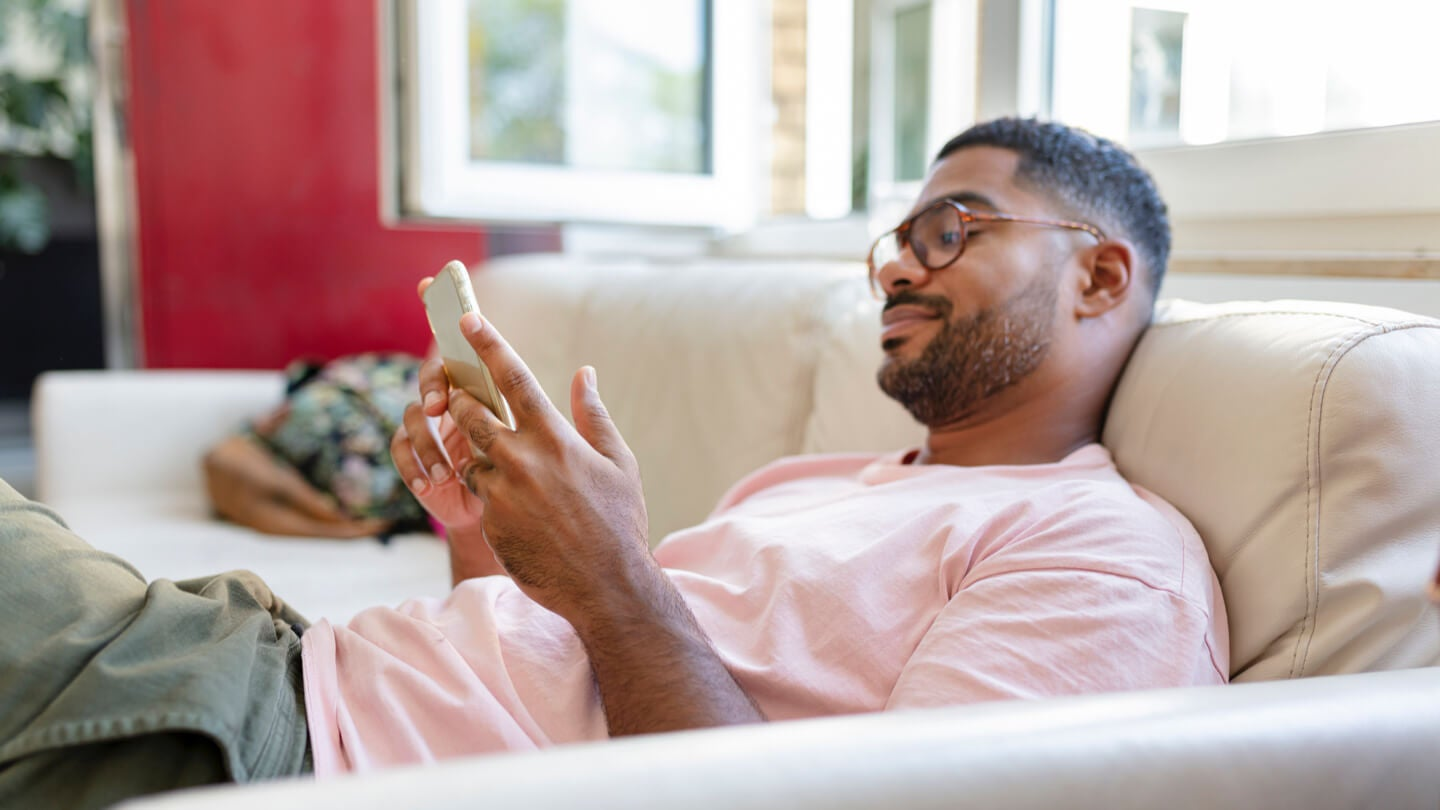 Man lying on his couch and looking at his phone