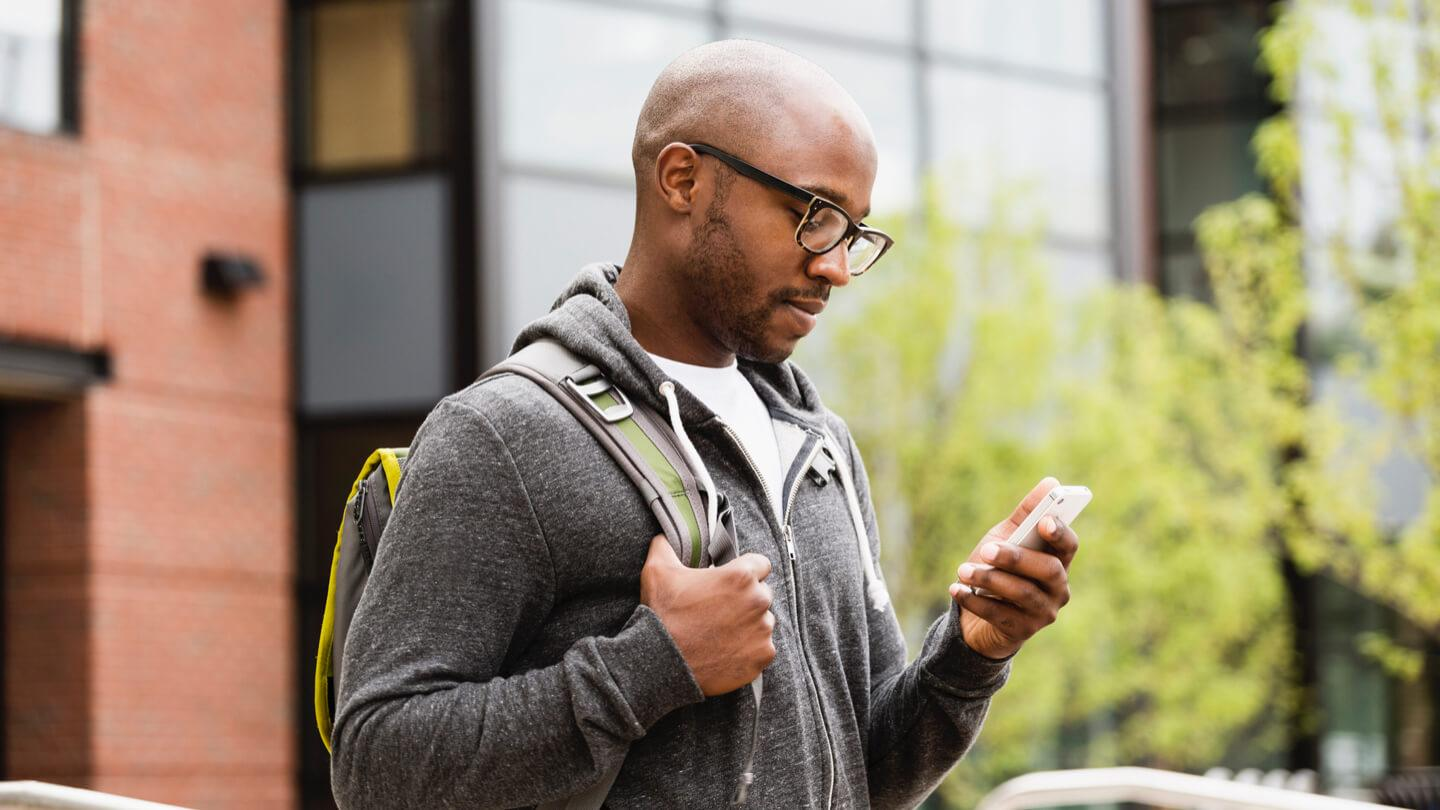 Image of man in glasses looking down at his phone