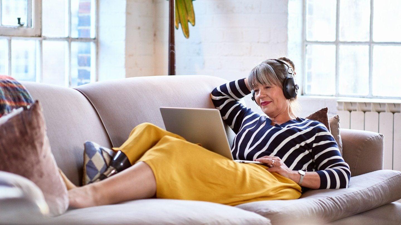 Senior woman wearing headphones watching movie on laptop - stock photo