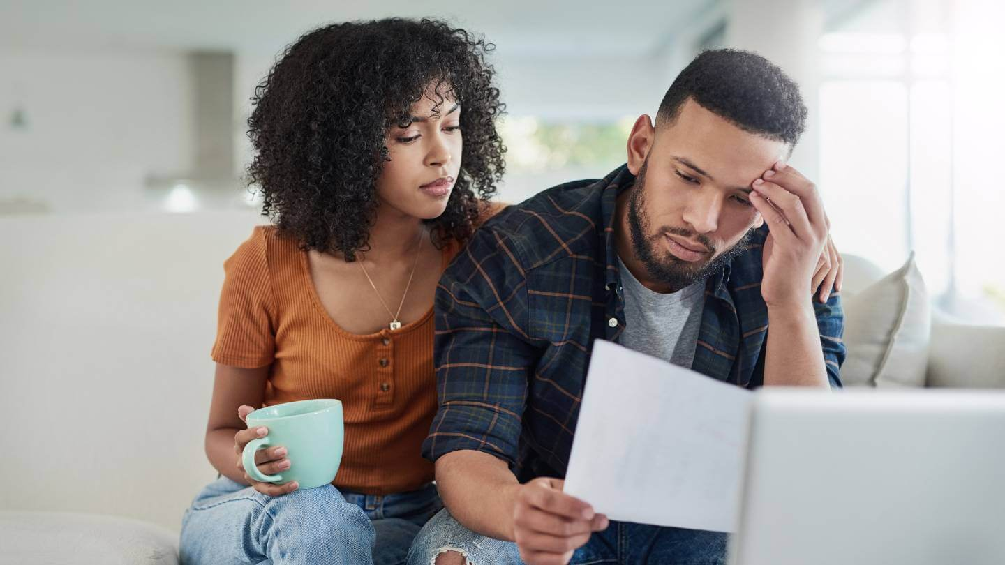 Young couple looking stressed about finances