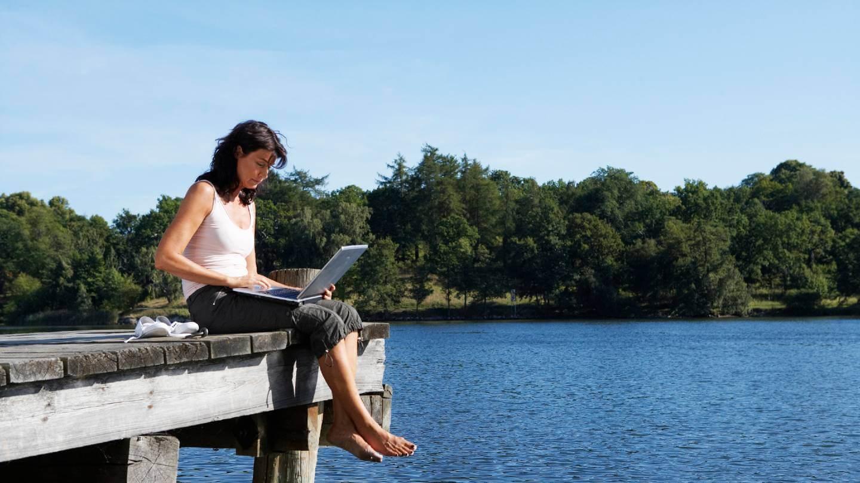 woman on computer outside lake