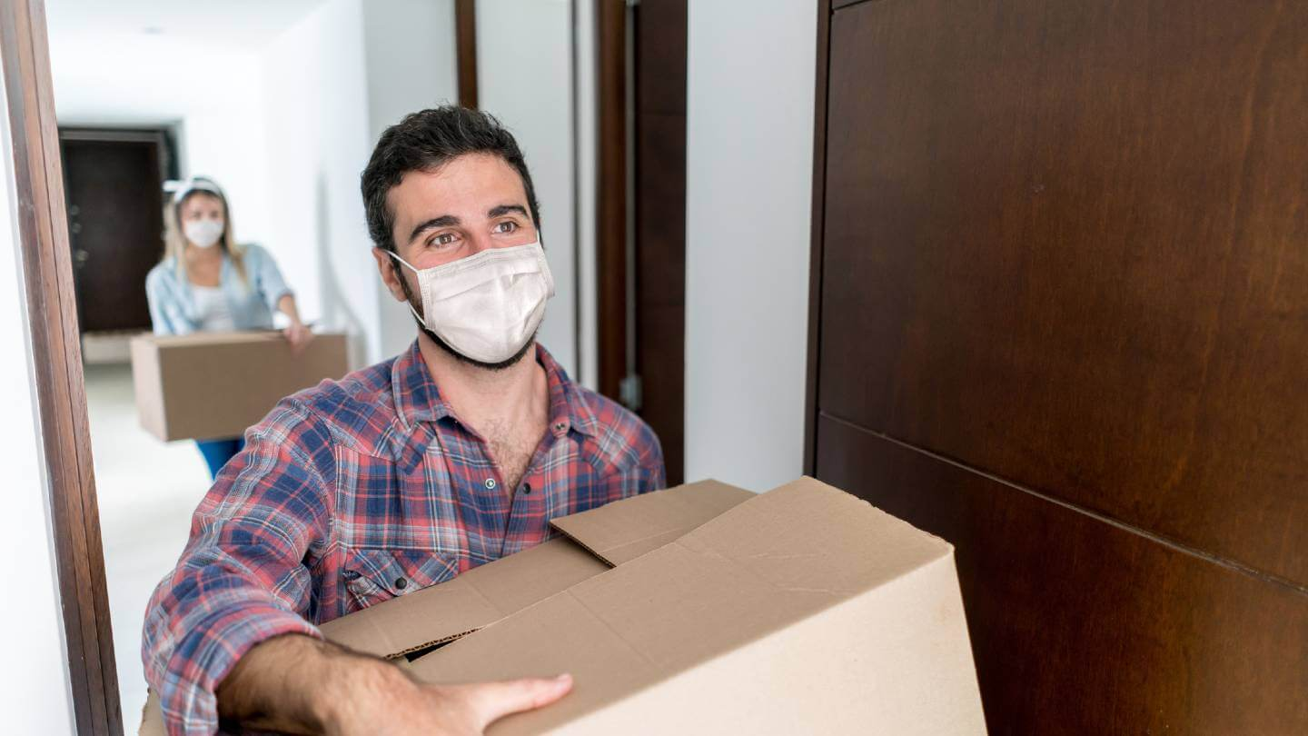 man carrying box with mask on