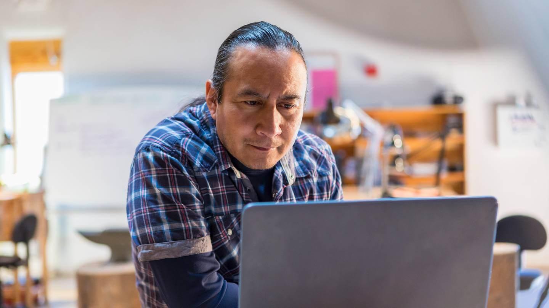 Native American man looking at laptop