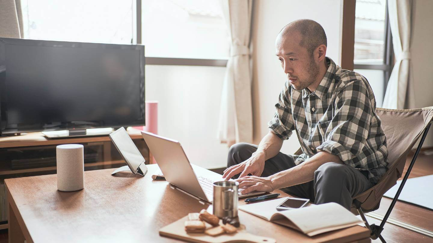 Man looking at computer on coffee table