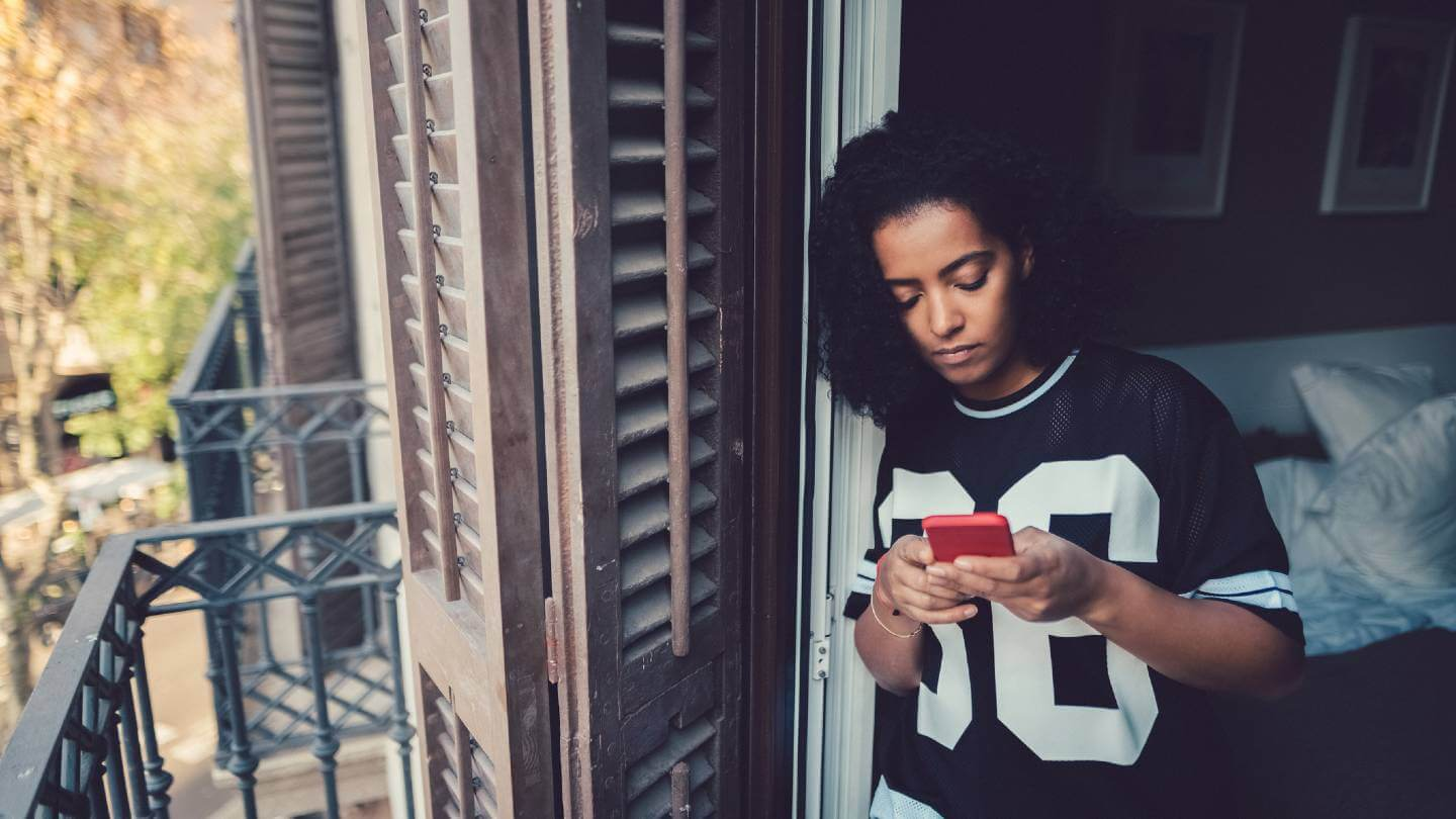 Woman on her phone looking upset in apartment