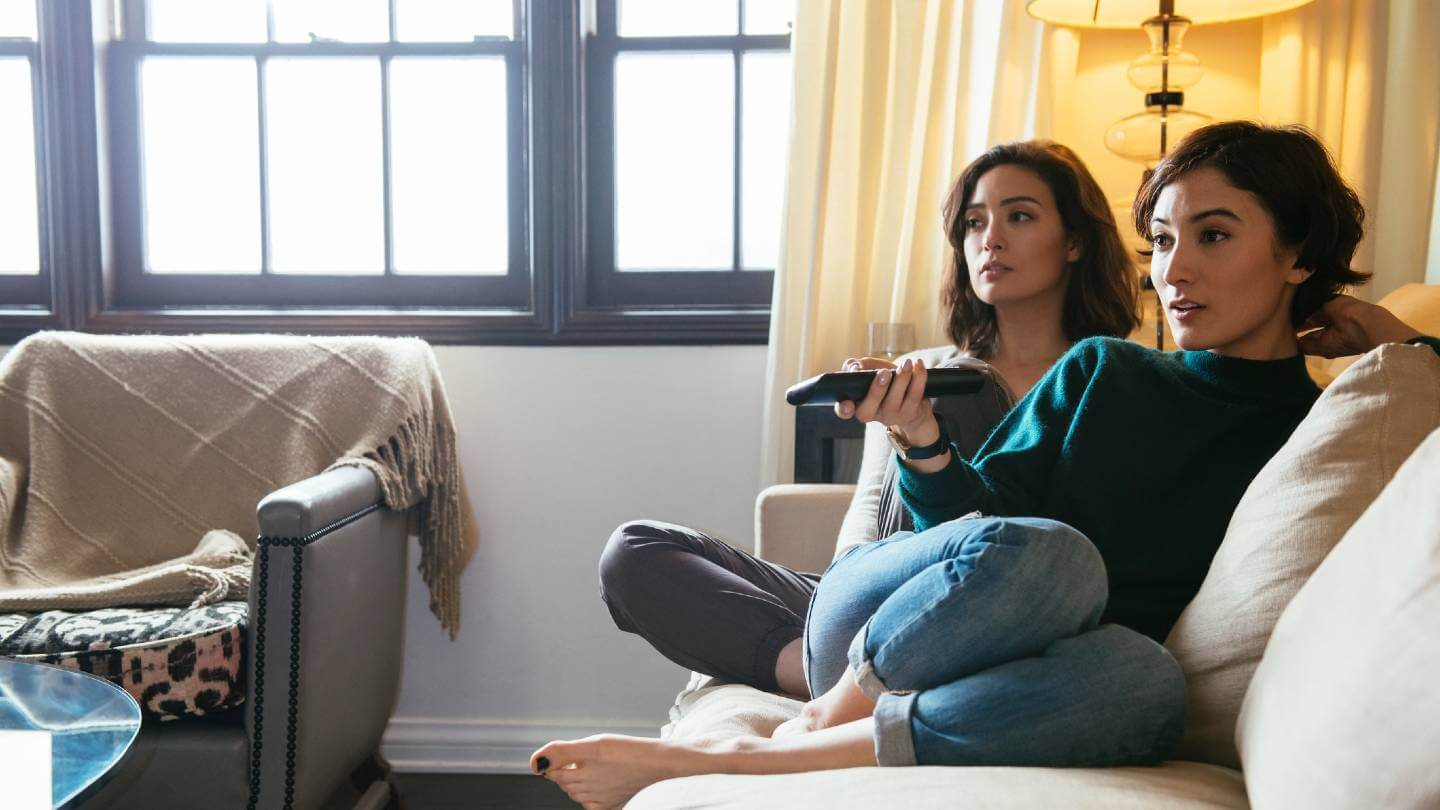 two women watching TV on couch