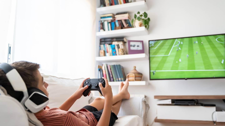 Boy online gaming in living room