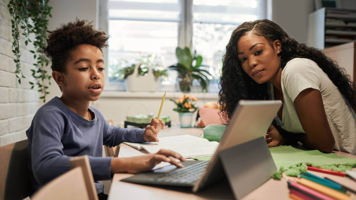 Woman assisting child with online homework
