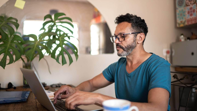 Mature man using laptop to work at home