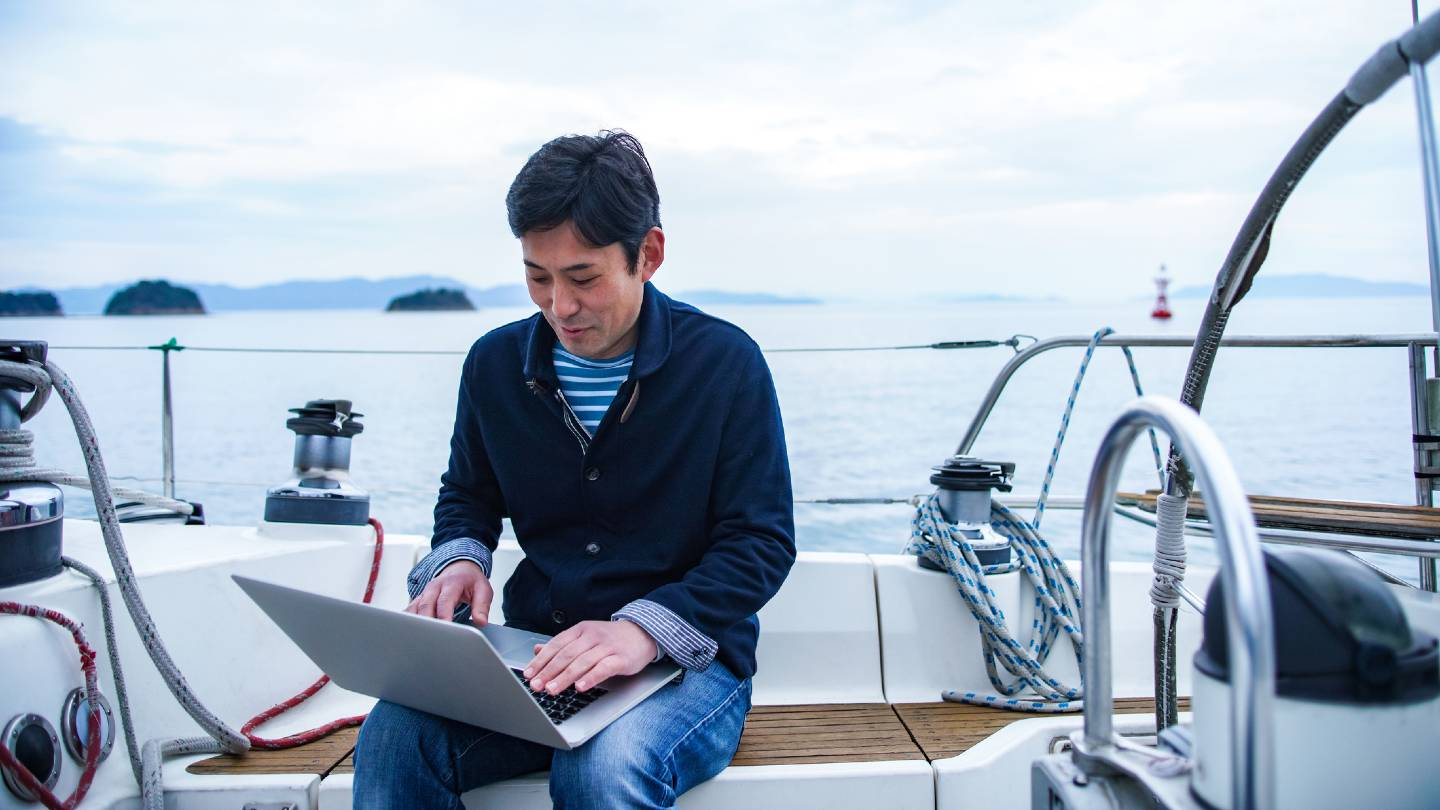 Middle-aged man using a laptop on a boat.