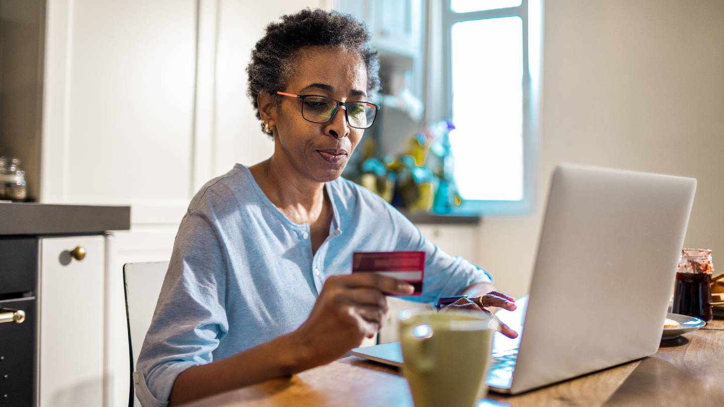 Senior woman sitting at a table holding credit card while looking at a laptop