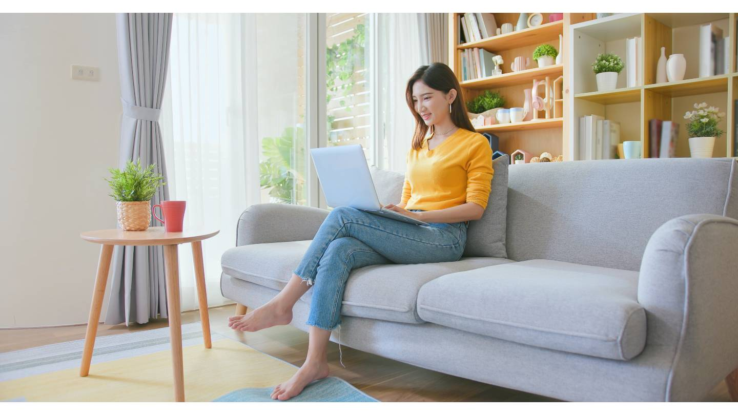 young asian woman using laptop computer checking social media feeling happy smiling while sitting on sofa when relax at home