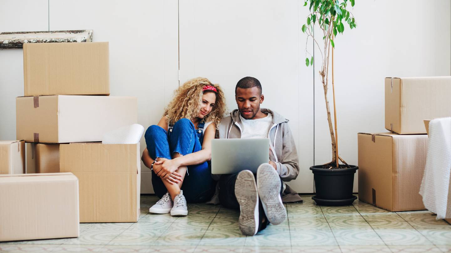 Couple sitting on floor with laptop, surrounded by moving boxes.