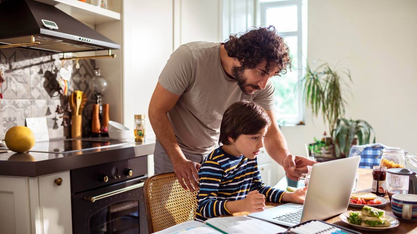 Dad helping son with homework on computer