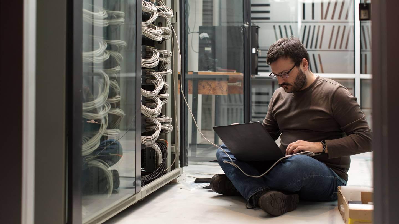 man looking at computer server