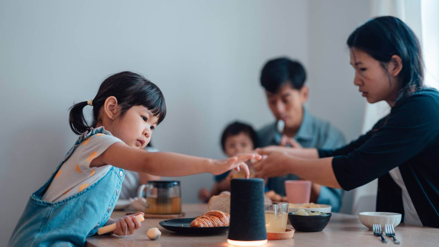 family at table with smart speaker
