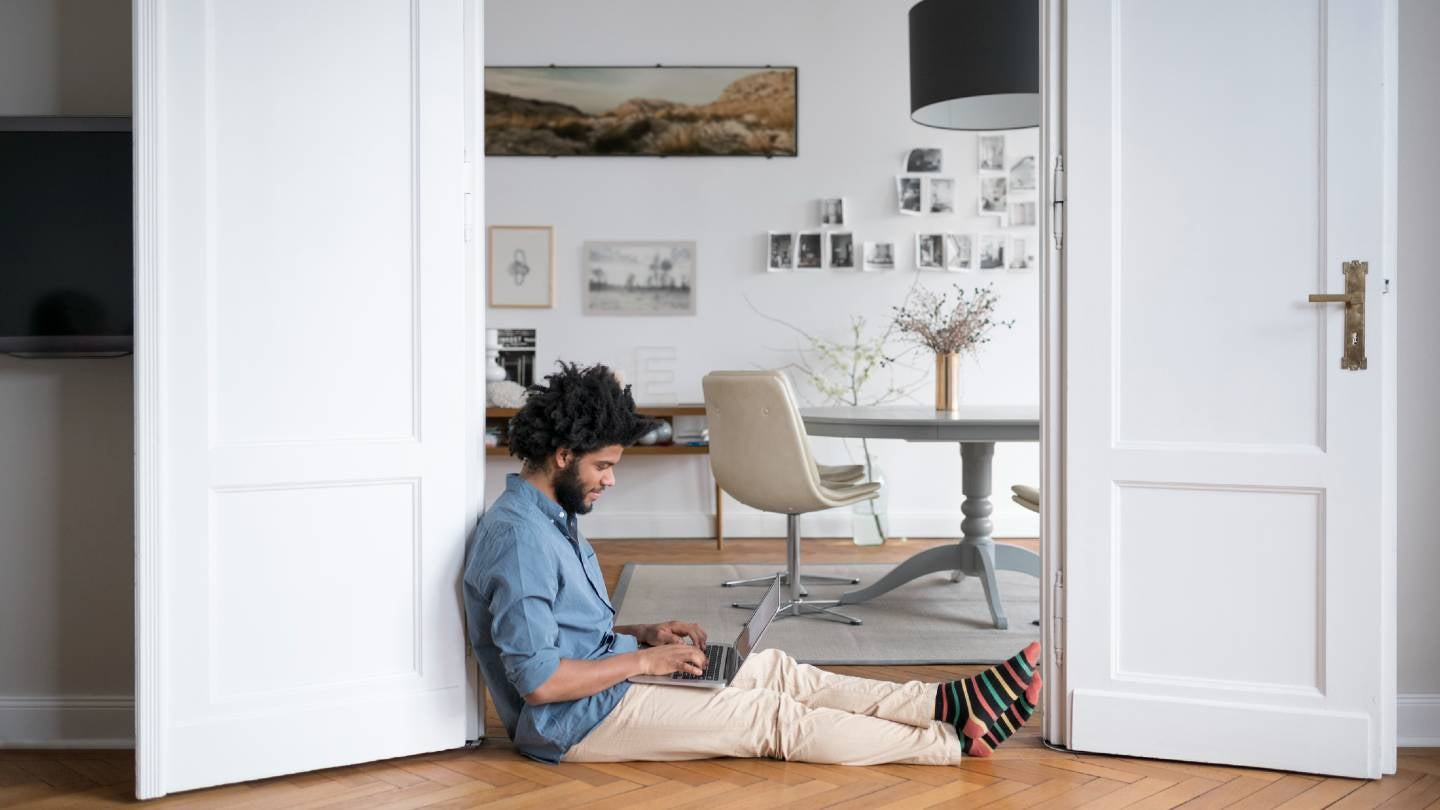 Young male sitting on floor of apartment working on laptop